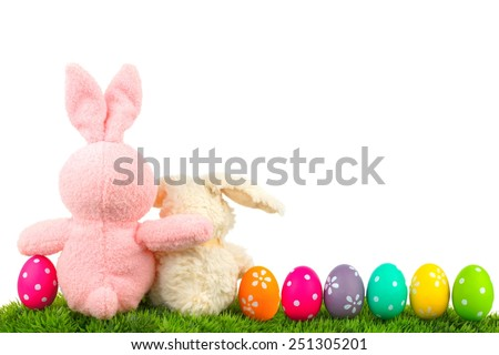 Hugging Easter bunnies on grass with colorful egg border over white, behind view - stock photo