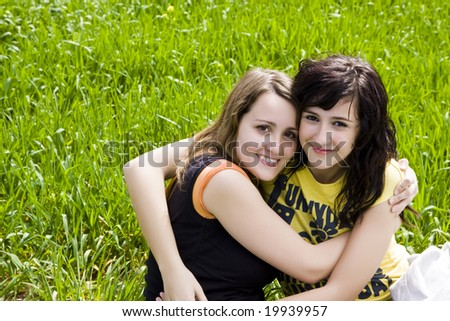 Hugging female friends in a meadow - stock photo