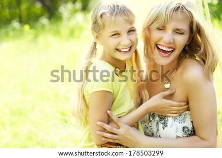 hugging happy mother and daughter for a walk in the park on a light green background