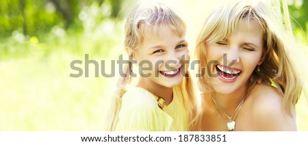 hugging happy mother and daughter for a walk in the park on a light green background. banner - stock photo