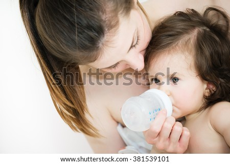 Hugging mom and baby, baby drinks a water from a bottle.Shallow doff - stock photo