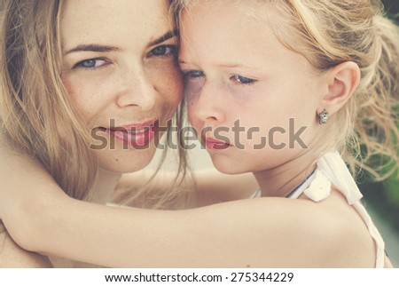 Hugging smiling mother and daughter. Family, child and happiness concept. Toned image - stock photo