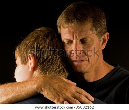 Hugging son, father cries (death, divorce, family fight, or similar) - stock photo
