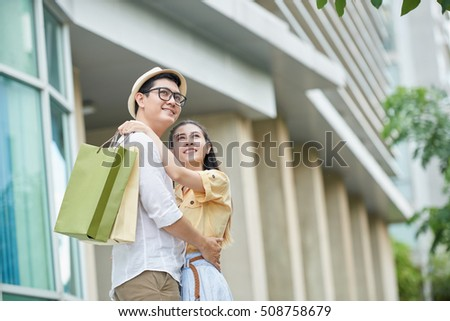 Hugging Vietnamese young couple standing outdoors