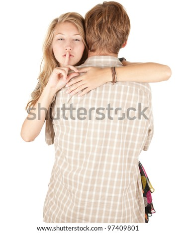 hugging young couple, girl with finger on mouth, keeping silence - stock photo