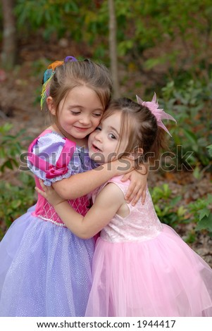 Hugs - Princess Sisters give each other a big hug while playing dress-up outdoors - stock photo