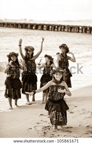 Hula girls on the beach processed in aged sepia - stock photo