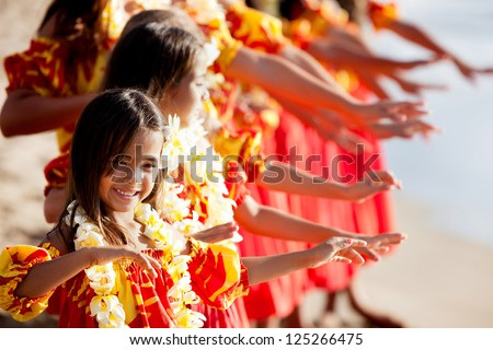 Hula girls on the beach with Hands raised - stock photo