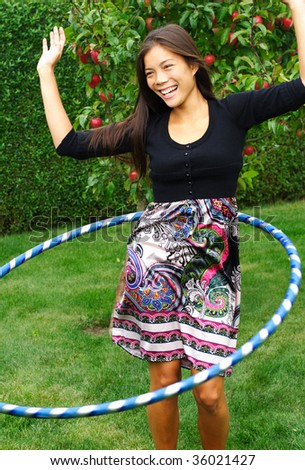 Hula hoop. Beautiful young woman doing hula hoop outdoors in the fall. - stock photo