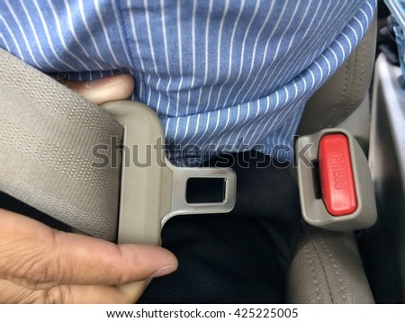 Human buckling seat belt in car  - stock photo