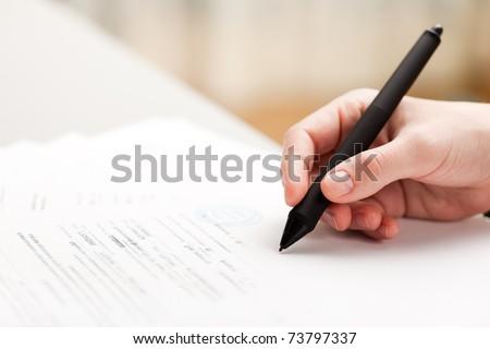 Human business men hand pen writing paper document - stock photo