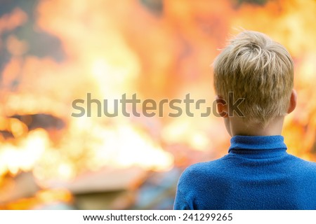 Human child boy at burning house fire accident background - stock photo
