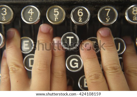 Human child hand prints on retro typewriter. Close up.  - stock photo
