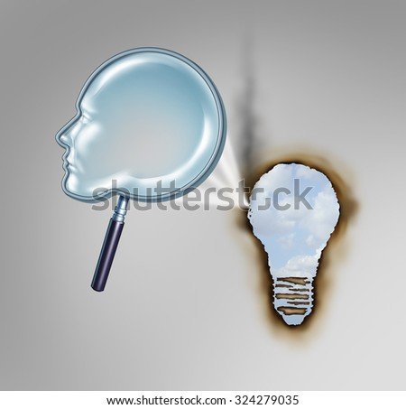 Human creativity concept as a magnifying glass shaped as a head profile creating a hot beam of light burning a hole in paper in the shape of a light bulb as a metaphor for creative thinker. - stock photo