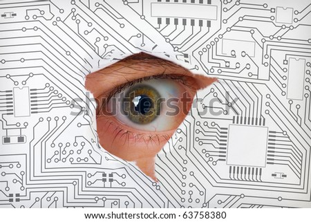 Human eye looking through a hole in the electronic circuit - stock photo