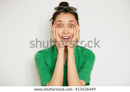 Human face expression and emotions. Headshot of young shocked female student looking at the camera, surprised with big sale prices, receiving some sensational news, holding her face with both hands - stock photo