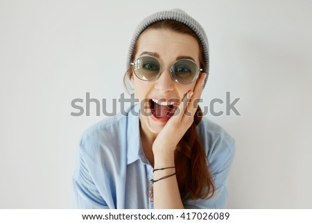 Human face expressions and emotions. Isolated headshot of student girl looking in surprise with hand on her cheek, mouth wide open. Young woman astonished with sale prices or some incredible news - stock photo