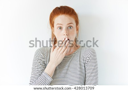 Human face expressions and emotions. Portrait of young desperate redhead woman in sailor shirt looking  panic, holding her head with both hands, with mouth wide open. Female in despair and shock - stock photo