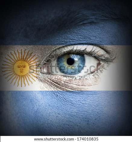 Human face painted with flag of Argentina - stock photo