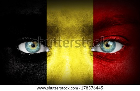 Human face painted with flag of Belgium - stock photo