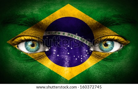 Human face painted with flag of Brazil - stock photo