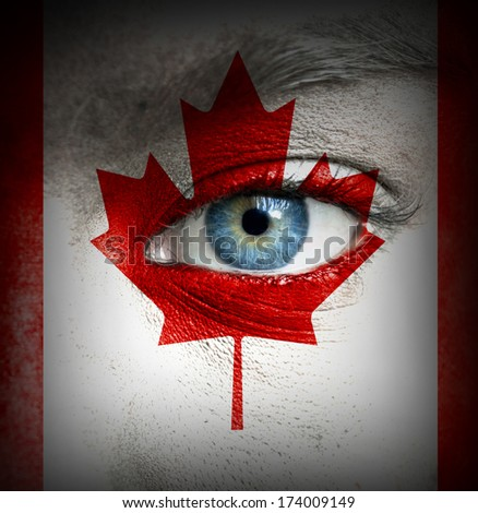 Human face painted with flag of Canada - stock photo