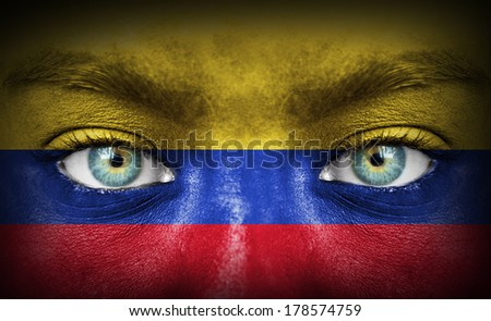 Human face painted with flag of Colombia - stock photo