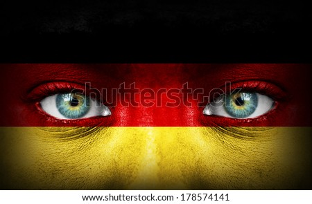 Human face painted with flag of Germany - stock photo