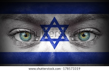 Human face painted with flag of Israel - stock photo