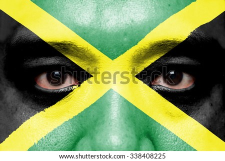 Human face painted with flag of Jamaica. - stock photo