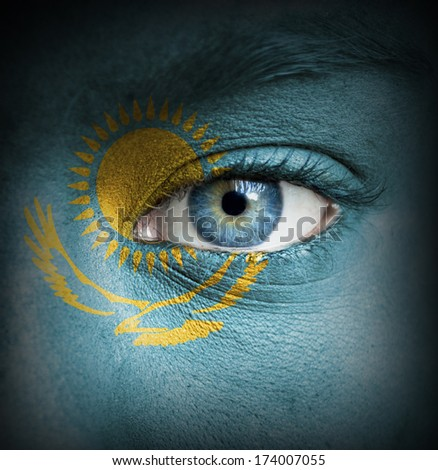 Human face painted with flag of Kazakhstan - stock photo