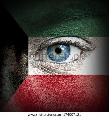 Human face painted with flag of Kuwait - stock photo