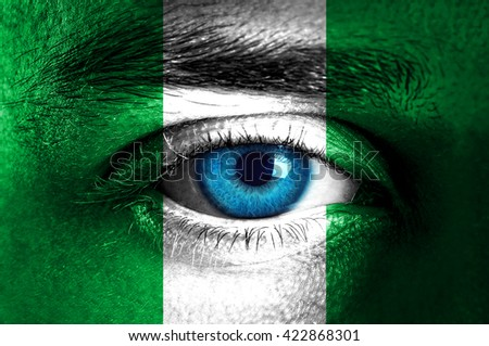 Human face painted with flag of Nigeria  - stock photo