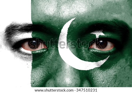 Human face painted with flag of pakistan. - stock photo