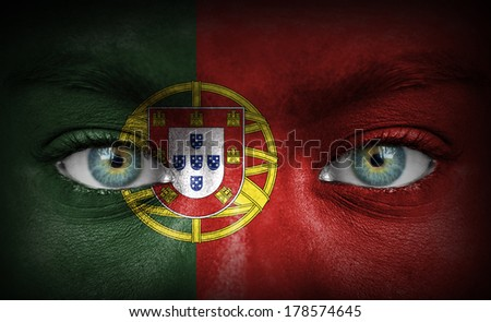 Human face painted with flag of Portugal - stock photo