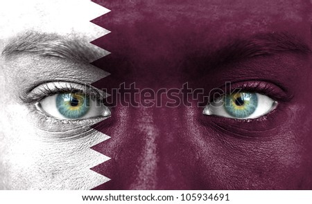 Human face painted with flag of Qatar - stock photo