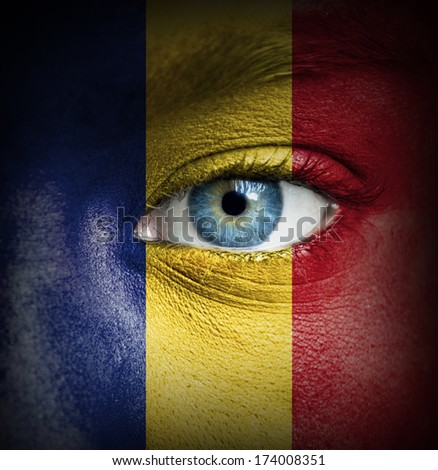 Human face painted with flag of Romania - stock photo