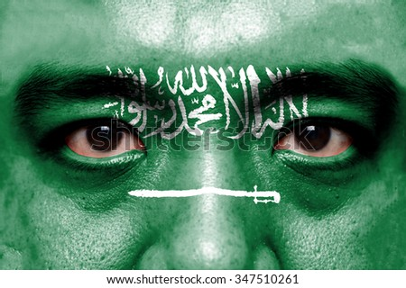 Human face painted with flag of Saudi Arabia. - stock photo