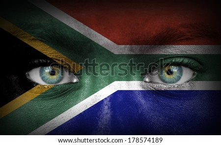 Human face painted with flag of South Africa - stock photo