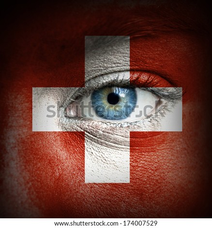 Human face painted with flag of Switzerland - stock photo