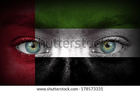 Human face painted with flag of United Arab Emirates - stock photo