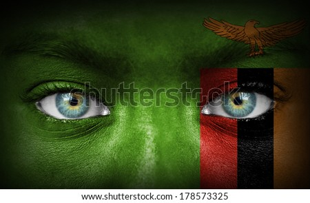 Human face painted with flag of Zambia - stock photo