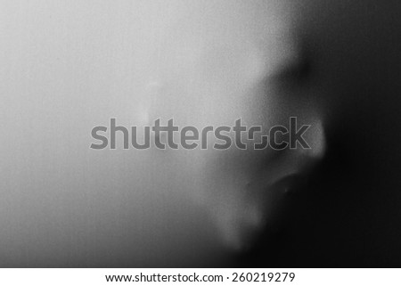 Human face screaming pressing through fabric as horror background - stock photo