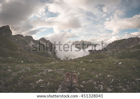Human feet with hiking boots lying on grass at the top of alpine valley with scenic clouds glowing at sunset. Relax while looking at view. The Alps, summer adventure, travel destination. Toned image. - stock photo