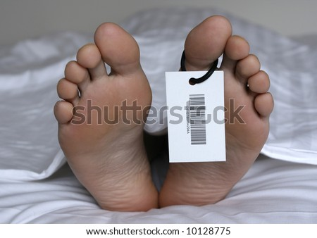 Human feet with toe tag - stock photo