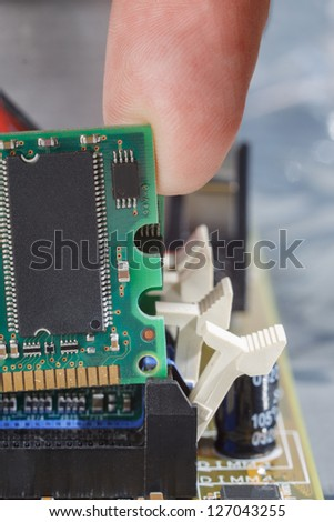 Human finger guides a memory module into the slot on the mother board.