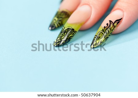 Human fingers with beautiful manicure in natural green style over blue - stock photo