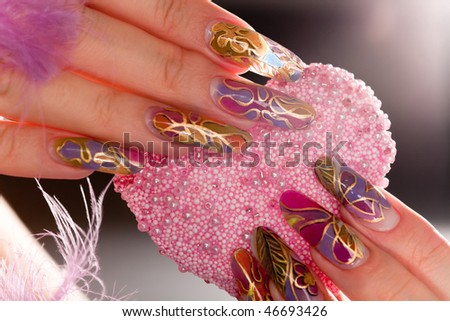 Human fingers with long acrylic fingernail and beautiful manicure holding pink heart - stock photo