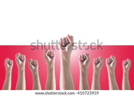 Human fist gesture among blur arm group Republic of Poland country flag pattern background Clenched hand raising up strong bunch of five Strengthening empowering conceptual idea Polish May Labour day - stock photo