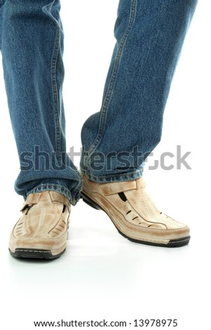 Human foot with brown leather shoes and jeans, isolated on white - stock photo